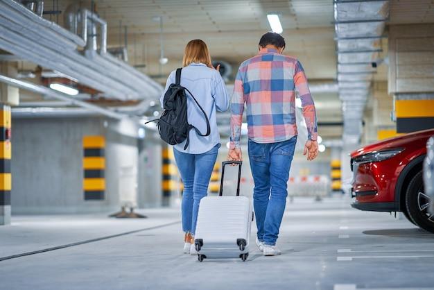 Пара туристов на подземной стоянке аэропорта
