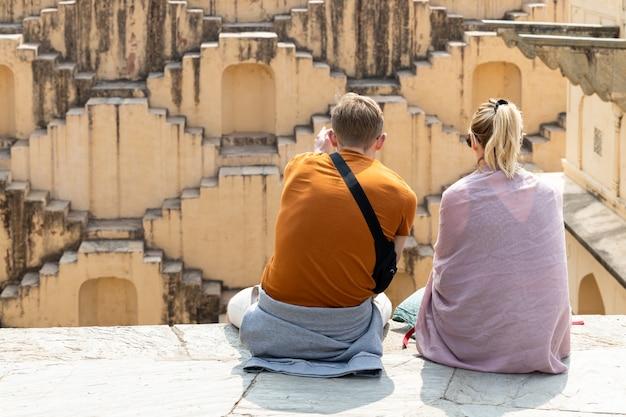 Пара туристов изучает древний индийский шаг хорошо, архитектура лестниц на stephan abhaneri baori в джайпуре, раджастхане индии.