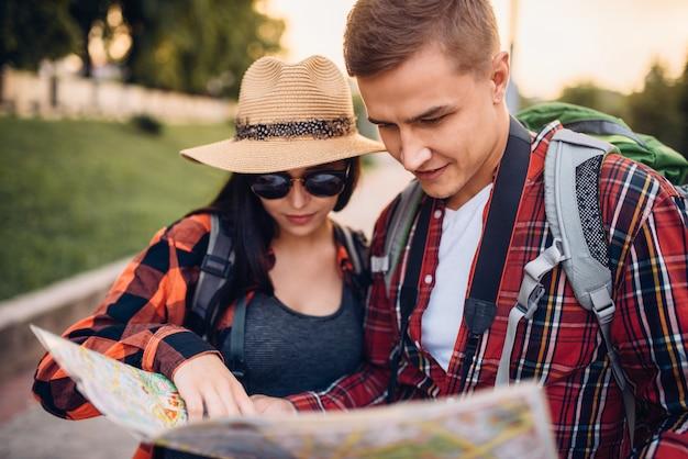 지도에서 도시 명소를 찾는 관광객 커플, 마을 여행. 여름 하이킹. 젊은 남녀의 하이킹 모험