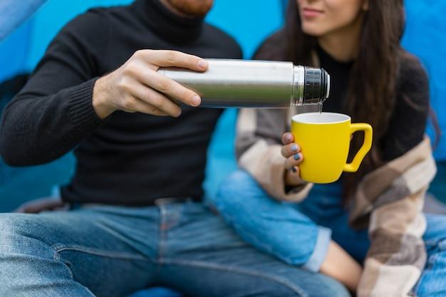 Пара туристов наливает чай из термоса