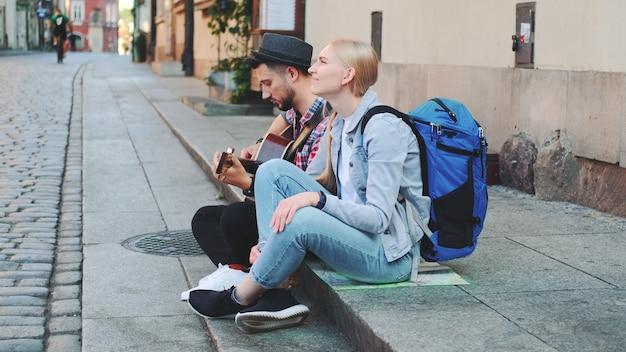 Пара туристов сидит на тротуаре, играет на гитаре и отдыхает