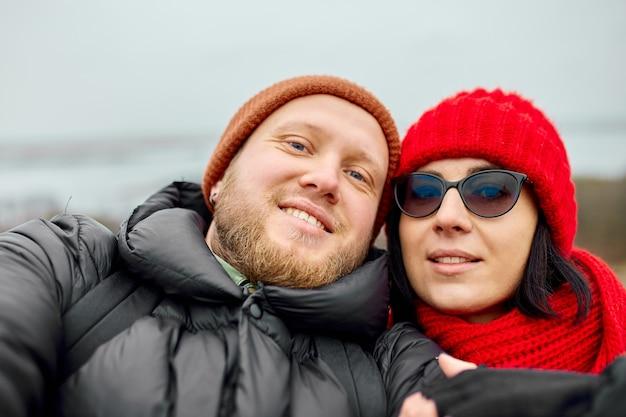 観光客のカップルが山で自分撮りをします