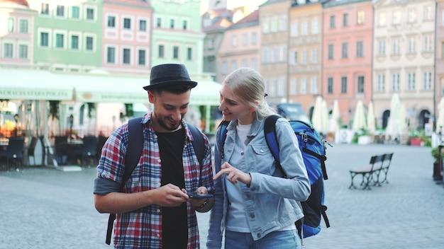 Пара туристов, использующих смартфон и любуясь красивыми окрестностями. рано утром они собираются на экскурсию.