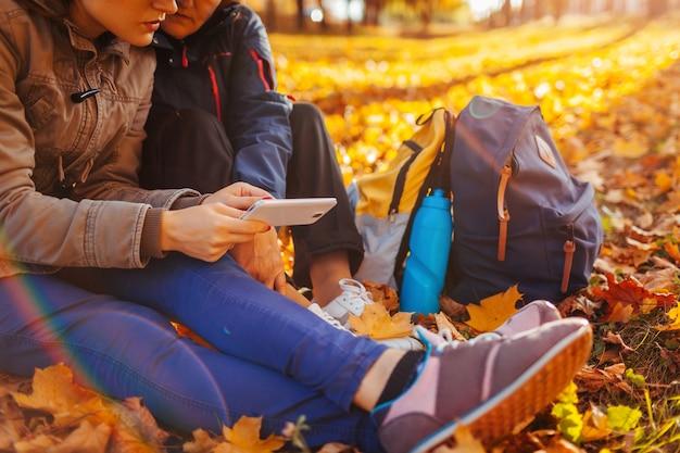 秋の森で電話でナビゲーターを使用して正しい方法を探しているバックパックを持つ観光客のカップル。休んでいる女性