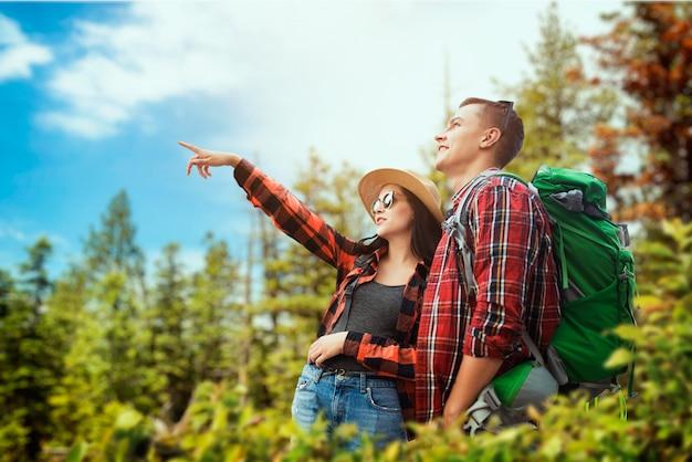 森の中を旅するバックパックで観光客のカップル。夏の森でのハイキング。若い男女のハイキングアドベンチャー