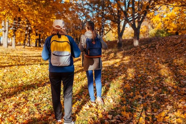 해질녘 가을 숲을 걷고 있는 배낭을 메고 관광객 몇 명. 함께 여행하는 낚시를 좋아하는 여성