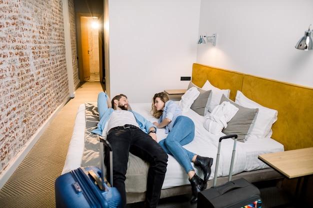 Пара туристов с большими чемоданами отдыхает после поездки лежа на кровати в гостиничном номере на каникулах
