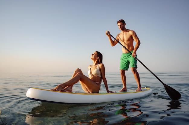바다에서 패들보드를 즐기는 젊은 남녀 관광객 커플