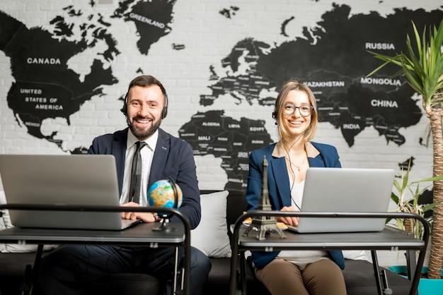 배경에 세계 지도가 있는 대행사 사무실에서 노트북과 헤드셋으로 온라인으로 작업하는 여행 관리자 몇 명