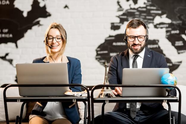 Пара менеджеров по путешествиям, работающих онлайн с ноутбуками и гарнитурами в офисе агентства на фоне карты мира
