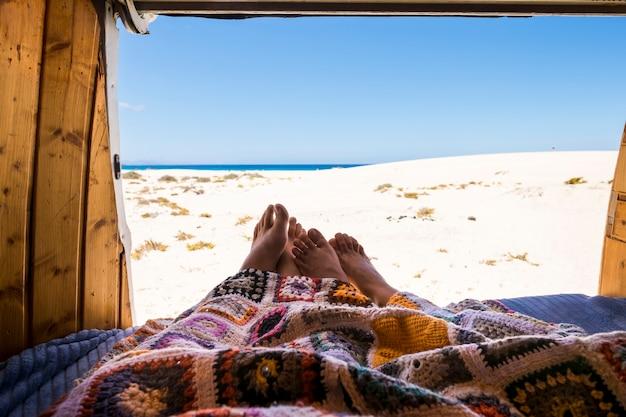 旅行者の足のカップルは、古い木製のヴィンテージバンとの代替の夏休みに旅行の放浪癖のライフスタイルを愛し、一緒に住んでいます