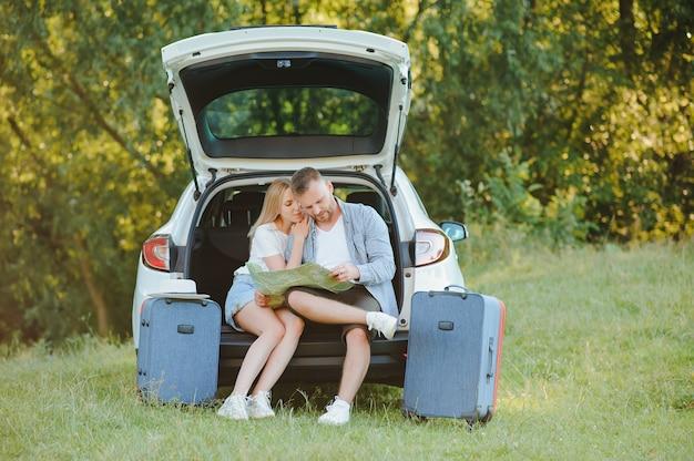 Пара путешественников, сидящих на хэтчбеке автомобиля у дороги во время отпуска.