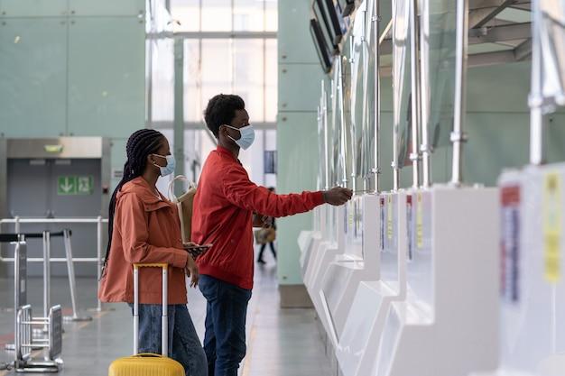 コロナウイルスの流行中の飛行前に空港のチェックインカウンターでマスクをした旅行者のカップル