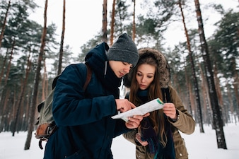 Couple of travelers looking at the map in winter forest. Travel concept
