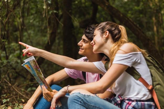 ジャングルに座っている旅行者のカップルが地図を見て、場所を示します