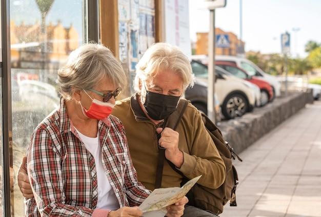 외과용 마스크를 쓰고 버스를 기다리는 동안 벤치에 앉아 있는 여행자 몇 명이 지도를 참조합니다.