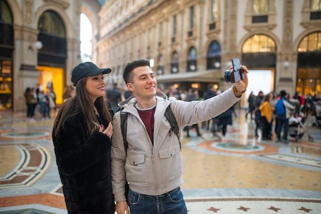 Пара туристов, делающих селфи в городе милан, италия