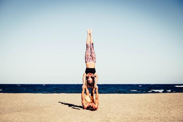 ビーチで一緒にアクロヨガをしている2人のアクティブでフィットネスの大人のカップル-男は彼のガールフレンドを足で持って砂の上に横たわっていました