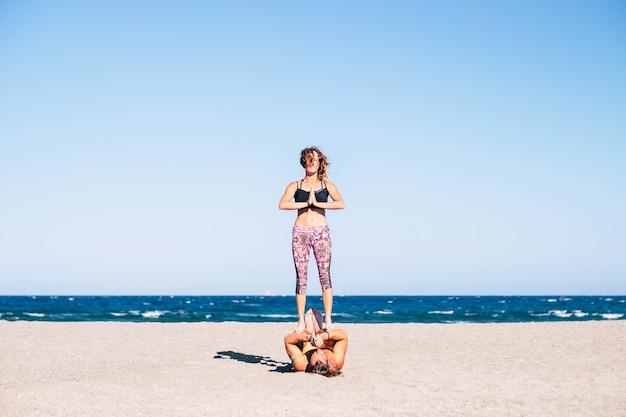 砂浜のビーチで一緒にアクロヨガをしている2人の大人のカップル-彼の足で彼のチームメイトを保持している男
