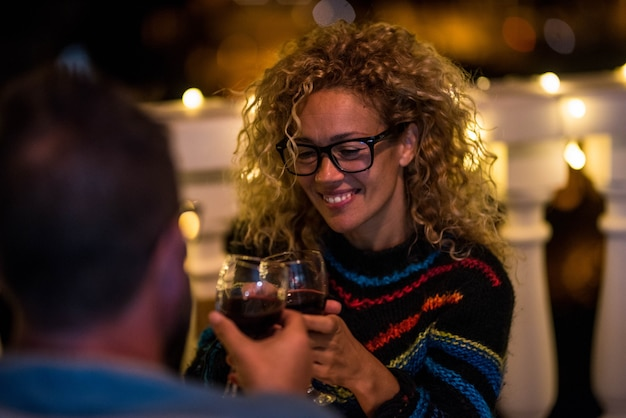 間の予定会議で2人の大人のカップル-楽しんでいるワインのカップと一緒にチャリンという音を立てる男性と女性