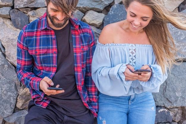 Пара из двух взрослых, использующих свои телефоны вместе на открытом воздухе - концепция технологий и образ жизни в интернете - красивая женщина и красивый мужчина веселятся вместе