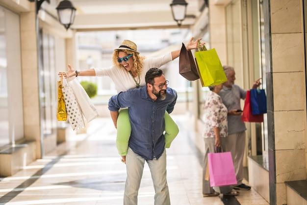 Пара из двух взрослых, идущих вместе, держа сумку для покупок в торговом центре - мужчина, держащий женщину, идущую по магазинам