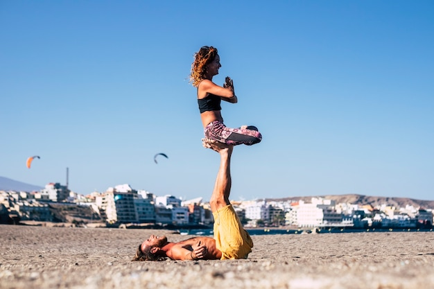アクロヨガと呼ばれるヨガのようなビーチドンのエクササイズでの2人のadutlytsのカップル-男性は足と足を空中に持って女性を抱いて砂の上に横たわっていました