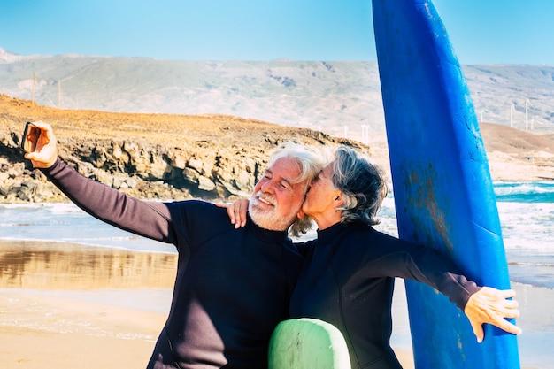 Пара из двух симпатичных пожилых людей и пенсионеров, делающих упражнения и делающих селфи со своими водными предметами и гидрокостюмами - женщина, целующая своего мужа