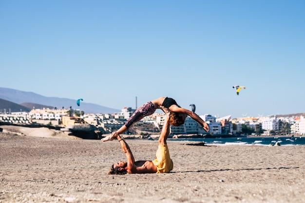 砂浜のビーチで一緒にエクササイズをしている2人のフィットネスとアクティブな人々のカップル-健康のためにアクロヨガをしている大人の女性と男性