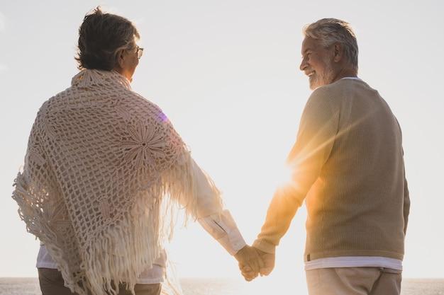 행복하고 활동적인 두 노인 부부는 일몰을 배경으로 손을 잡고 해변에서 함께 여름을 즐기고 있습니다.