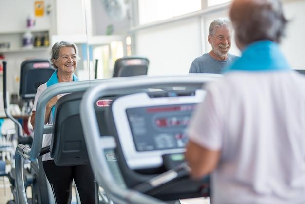Пара из двух счастливых и здоровых пожилых людей вместе делает упражнения в тренажерном зале, бегая по тапису - активный образ жизни