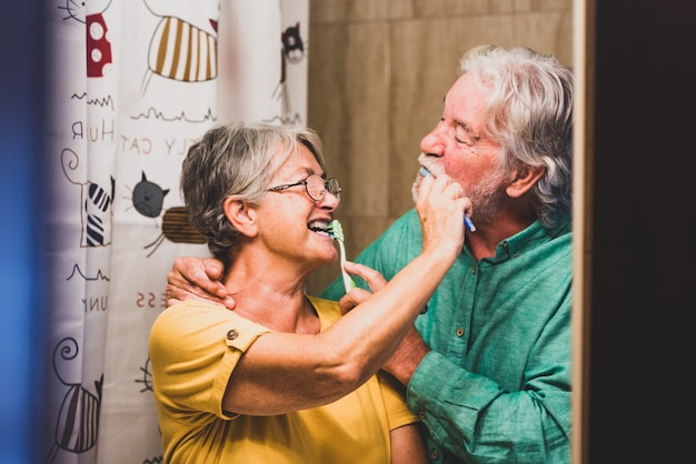幸せで笑顔の2人の先輩のカップルが自宅のバスルームで一緒に歯を磨いています-セルフケアと自分の世話をしています
