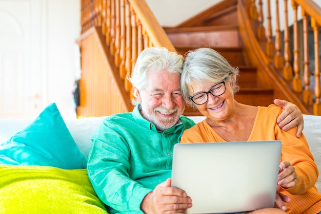 집에 있는 두 명의 행복한 노년층 또는 노인 부부가 소파에 앉아 노트북이나 컴퓨터를 보고 함께 즐겁게 놀고 있습니다.