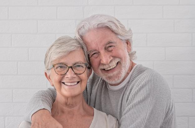 笑顔で家で抱き締めて立っているカメラを見ている2人の幸せな高齢者のカップル