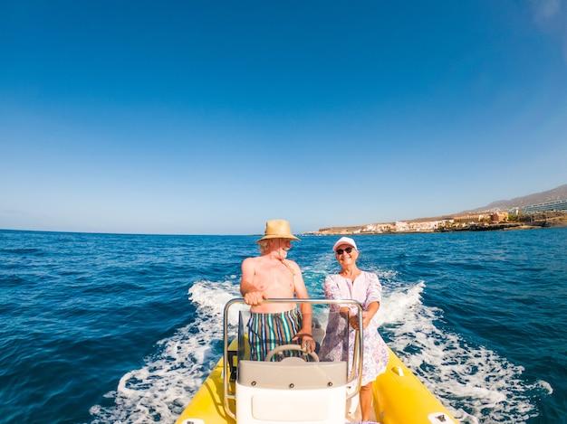 작은 보트나 작은 배를 사용하고 운전하는 두 명의 행복한 노인과 성숙한 사람들