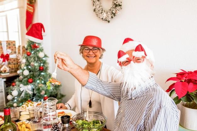 昼食時にクリスマスの日を食べて楽しんでいる2人の幸せな先輩のカップル-背景のクリスマスツリー-テーブルで一緒に笑って笑っている-ひげマスクを楽しんでいる老人