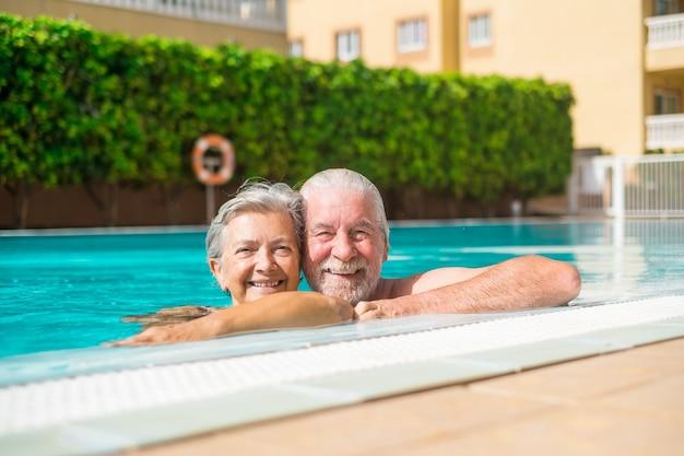 두 명의 행복한 노인 부부가 수영장에서 함께 웃고 카메라를 바라보며 즐거운 시간을 보내고 있습니다. 물 속에서 야외에서 여름을 즐기는 행복한 사람들