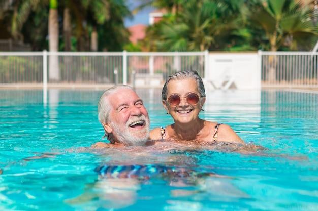 두 명의 행복한 노인들이 수영장에서 웃고 노는 것을 함께 즐기고 있습니다. 물 속에서 야외에서 여름을 즐기는 행복한 사람들