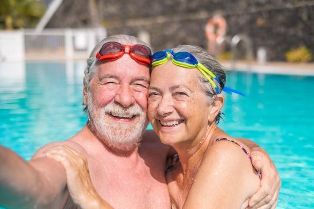 두 명의 행복한 노인 부부가 수영장에서 함께 웃고 카메라를 바라보며 셀카 사진을 찍고 있습니다. 물 속에서 야외에서 여름을 즐기는 행복한 사람들