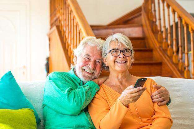 Пара двух счастливых пожилых людей сидит на диване дома, смотрит телевизор и борется за пульт дистанционного управления телевизором
