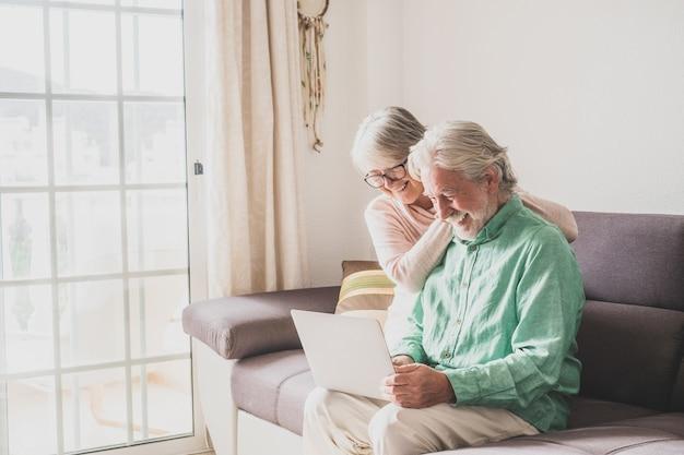 집에서 함께 노트북을 사용하는 행복한 두 노인 부부는 소파에 앉아 웃고 즐겁게 인터넷 서핑을 하고 있습니다.