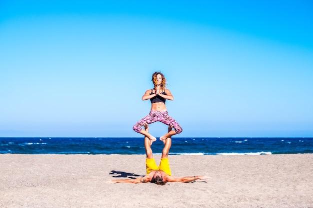 砂浜のビーチで一緒にエクササイズをしている2人の健康でフィットネスの大人のカップル-アクロヨガをしている2人