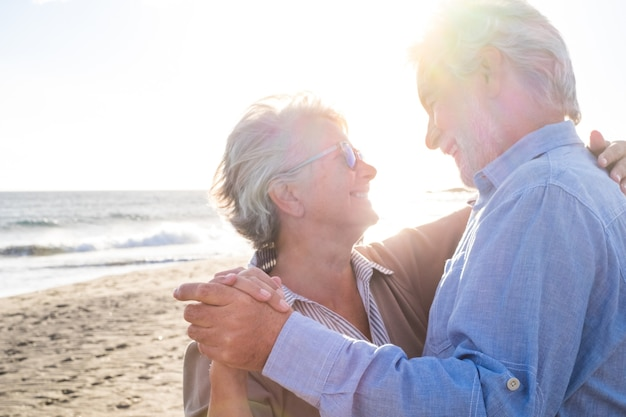 일몰을 배경으로 모래 해변에서 함께 여름 춤을 즐기는 두 명의 늙고 성숙한 행복한 노인 부부. 은퇴 및 여가 생활 방식