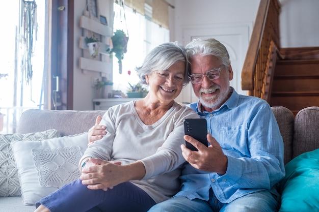 Пара двух старых и зрелых людей дома, используя планшет вместе на диване. старший использовать ноутбук с удовольствием и с удовольствием смотрит на него. концепция досуга и свободного времени