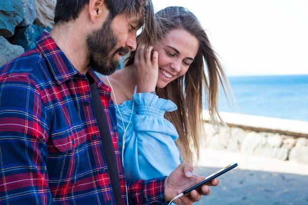 Пара из двух человек вместе, использующих телефон и слушающих музыку на одном телефоне - девочка и мальчик веселятся, улыбаются и смотрят на смартфон - интернет и концепция онлайн-устройства и образ жизни