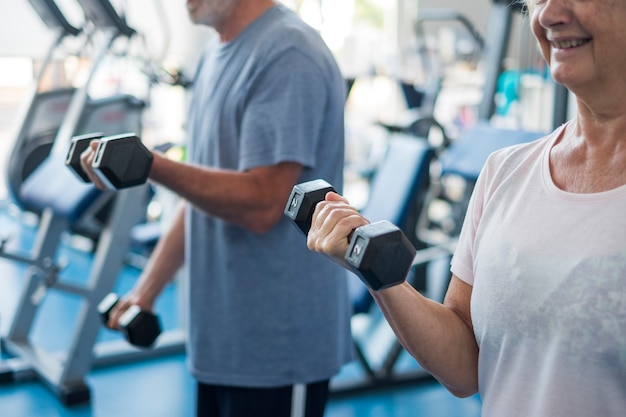 Пара из двух пожилых людей и зрелых людей в тренажерном зале, выполняющих упражнения - взрослые вместе держат гантели и работают на бицепсы