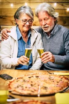 夕食時に一緒にピザとビールを食べたり飲んだりする2人の高齢者と成熟した人々のカップル-2人の年金受給者がチャリンという音を立てて楽しんでいます