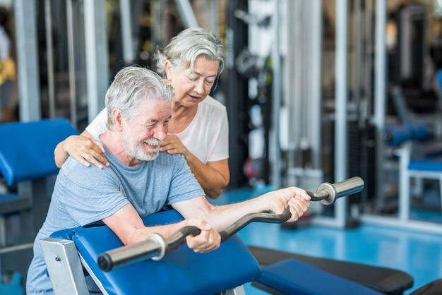Пара из двух пожилых людей в тренажерном зале вместе делает упражнения, развлекаясь, чтобы быть здоровым и подтянутым - мужчина держит штангу без веса и с женой помогает ему