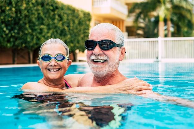 スイミングプールの水に抱きしめられた2人の先輩のカップル-プールで一緒に運動をしているアクティブな男性と女性-愛を込めて抱きしめられた-ゴーグルを着用