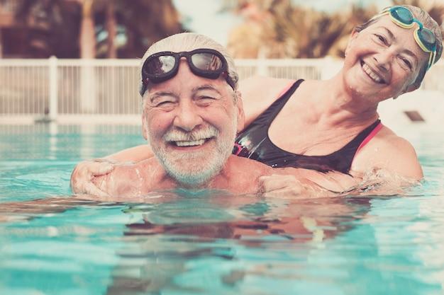 スイミングプールの水に抱きしめられた2人の先輩のカップル-プールで一緒に運動をしているアクティブな男性と女性-愛を込めて抱きしめた